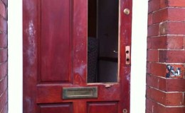 Wooden door with smashed panel, handles and locks